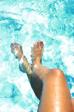 Tan golden legs of young woman and feet painted nails having suntan at swimming pool stock images