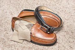Tan leather dress shoes. A new pair of tan leather shoes with socks and belt on beige carpet Royalty Free Stock Photography