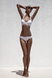 Tan model posing in bikini and sunglasses. Beautiful tan female model posing in bikini and sunglasses. Against white wall Royalty Free Stock Photography
