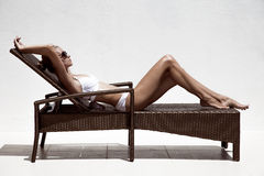 Tan model sunbathing in bikini on chaise-longue. Beautiful tan female model sunbathing in bikini on chaise-longue. Against white wall Royalty Free Stock Photo