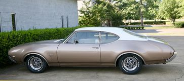 Tan Oldsmobile Cutlass Supreme. The Oldsmobile Cutlass Supreme is a mid-size car produced by Oldsmobile between 1966 and 1997. It was positioned as a premium Stock Photo