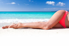 Tan slim legs on beach Stock Images