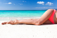 Tan slim legs on beach Stock Photo