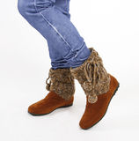 Tan suede boots. Tan suede flat boots are knit sweater-topped on a white backround royalty free stock photo