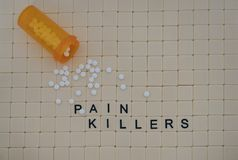 Tiles in a Row Spelling Pain Killers and White Tablets on a Tile. Tan tiles with black capital letters spelling pain killers set in a background of small tan Stock Photo