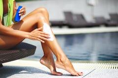 Tan woman applying sun protection lotion stock images