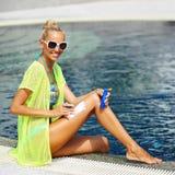 Tan woman applying sun protection lotion.  Royalty Free Stock Photo