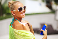 Tan woman applying sun protection lotion royalty free stock images