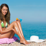 Tan woman applying sunscreen (focus on legs) Stock Photography