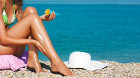 Tan Woman Applying Sunscreen on Legs Royalty Free Stock Photography