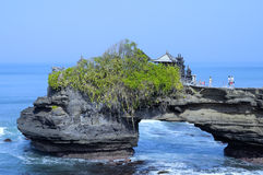 Tanah Lot Beach at Bali, Indonesia. Tanah Lot is a rock formation off the Indonesian island of Bali. It is home to the pilgrimage temple Pura Tanah Lot, a Stock Photo