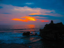 Tanah Lot and sea waves in golden sunset, Bali Stock Images