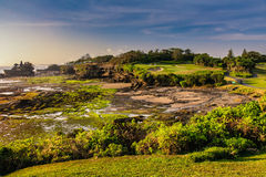 Tanah Lot Temple and Golf Course. Tanah Lot Temple in the middle of the ocean at sunset and low tide. Golf course near the temple Tanah Lot, Bali, Indonesia Royalty Free Stock Photography