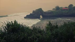 Tanah Lot Temple with green plant on the foreground stock video footage