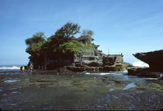 Tanah Lot Temple Indonesia. Windswept and wave battered Tanah Lot temple at low tide. One of seven sea god temples on the coast of Bali, Indonesia stock image