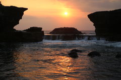Tanah Lot with water and temple at sunset Stock Photography