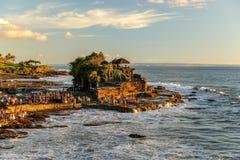 Tanah lotttempel i solnedgången som fördjupa in i havet i Bali Arkivbild