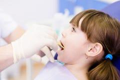 Tand het onderzoeken wordt gegeven aan meisje door tandarts Stock Afbeeldingen