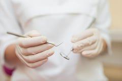 Tand- instrument i händerna av doktorn Tandläkaren i sterila latexhandskar som rymmer den tand- hjälpmedeldetaljen, skjuter Royaltyfri Fotografi