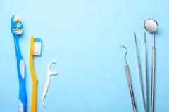 tand- instrument Tand- spegel, sondkrok, pincett och tandborste med floss på blått Royaltyfri Bild
