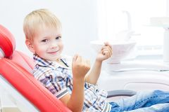 Tand kliniek Ontvangst, onderzoek van de patiënt Tandenzorg Een kleine jongen met tandzijde zit als tandvoorzitter royalty-vrije stock fotografie