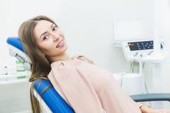 Tand kliniek Ontvangst, onderzoek van de patiënt Tandenzorg De jonge vrouw ondergaat een tandonderzoek door a royalty-vrije stock foto