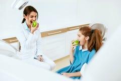 Tand kliniek Vrouwelijke Tandarts And Little Patient die Apple eten royalty-vrije stock foto