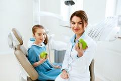 Tand kliniek Vrouwelijke Tandarts And Little Patient die Apple eten royalty-vrije stock afbeeldingen