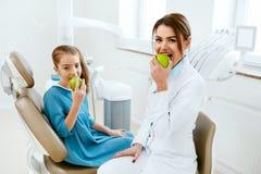 Tand kliniek Vrouwelijke Tandarts And Little Patient die Apple eten stock foto's