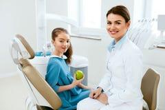 Tand kliniek Vrouwelijke Tandarts And Little Patient die Apple eten stock fotografie