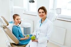Tand kliniek Vrouwelijke Tandarts And Little Patient die Apple eten stock afbeelding
