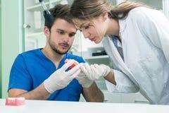 Tand- protes, tandproteser, prostheticsarbete Prostheticshänder, medan arbeta på tandprotesen, de falska tänderna, en studie och  Fotografering för Bildbyråer