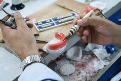 Tand- tekniker eller tandläkare som arbetar med tandtandproteser royaltyfri bild