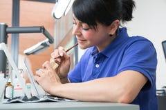 Tekniker i ett tand- laboratorium som applicerar keramik till en prosthesis royaltyfri bild