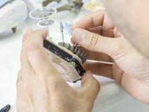 Tand- tekniker som gör en metallstruktur av en tand- krona eller Arkivbilder