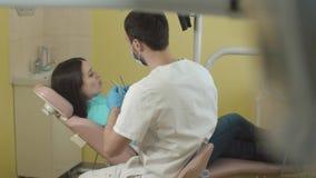 Tandarts aan het werk in het bureau jonge mooie vrouw op een bezoek aan de tandarts stock video
