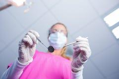 Tandarts in de chirurgische hulpmiddelen van de maskerholding over patiënt Stock Foto's