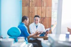 Tandarts die aan zijn patiënt bij tandzorgkliniek spreken Royalty-vrije Stock Foto