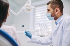 Tandarts die bij röntgenstraal aan de patiënt tonen royalty-vrije stock afbeelding