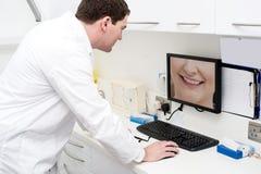 Tandarts die computer in tandkliniek met behulp van stock foto