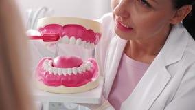 Tandarts die de juiste manier om tanden in de kliniek van de tandarts tonen te borstelen stock video