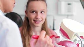 Tandarts die de juiste manier om tanden tonen te borstelen stock footage