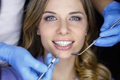 Tandarts die de tanden van een patiënt in de tandarts onderzoeken royalty-vrije stock afbeelding
