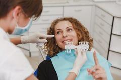 Tandarts die geduldige de tandenschaduw vergelijken van ` s met steekproeven voor blekenbehandeling royalty-vrije stock foto's