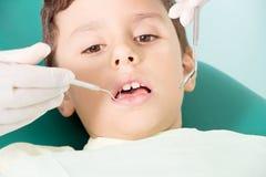 Tandarts die kid& x27 onderzoeken; s tanden stock foto's