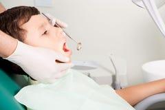 Tandarts die kid& x27 onderzoeken; s tanden royalty-vrije stock afbeeldingen
