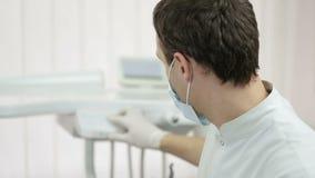 Tandarts die masker dragen en voor een geduldig onderzoek voorbereidingen treffen stock footage