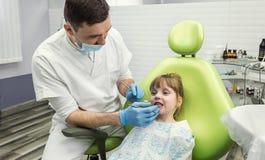 Tandarts die meisje` s tanden in kliniek onderzoeken Tandprobleem royalty-vrije stock afbeeldingen