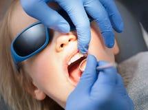 Tandarts die meisjestanden met tandspiegel in pediatrische tandkliniek onderzoeken stock afbeelding