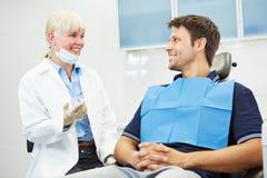 Tandarts die met patiënt op stoel spreken Stock Foto